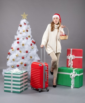 Front view blonde girl with santa hat holding basket with xmas toys and a valise