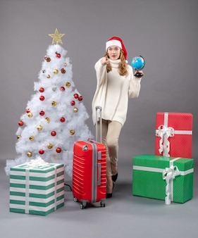 Front view blonde girl with santa hat holding globe near red valise