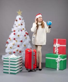 Вид спереди блондинка в шляпе санта-клауса держит глобус возле рождественской елки