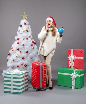 Front view blonde girl with santa hat holding globe telling something