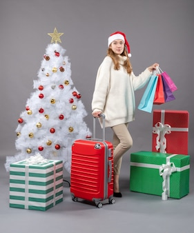 Вид спереди блондинка в шляпе санта-клауса держит красный чемодан и сумки для покупок