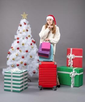 Ragazza bionda di vista frontale con il cappello della santa che tiene valise rossa e borse della spesa che mostrano il segno di shh