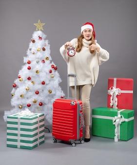빨간색 알람 시계를 보여주는 산타 모자와 전면보기 금발 소녀