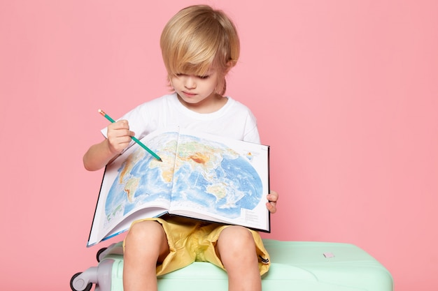 Front view blonde haired boy drawing map in white t-shirt on the pink floor