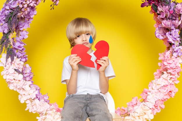 A front view blonde haired boy in white t-shirt with heart shape sitting on the flower made stand on the yellow floor