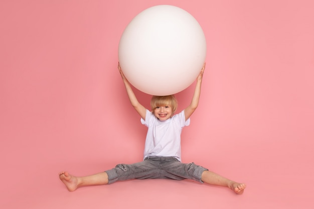 A front view blonde happy boy playing with white ball on the pink floor