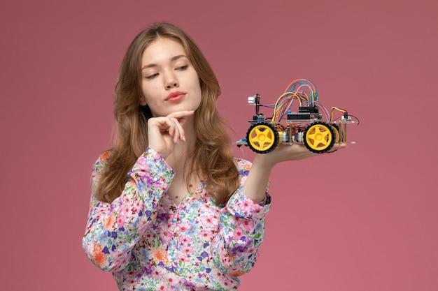 彼女の車のおもちゃを見ている正面図金髪の女性