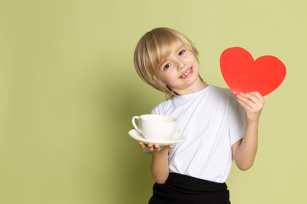 A front view blonde smiling boy in white t-shirt holding white cup and heart shape on the stone colored floor