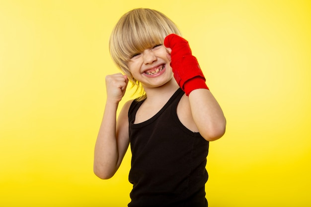 A front view blonde smiling kid in black t-shirt and posing boxing on the yellow wall
