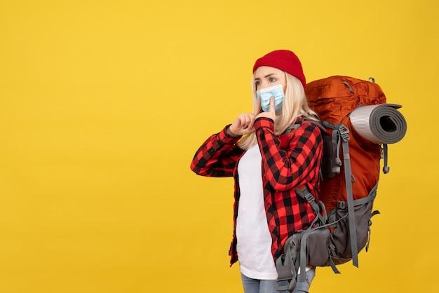 黄色の壁に立っている彼女のバックパックと正面図金髪旅行