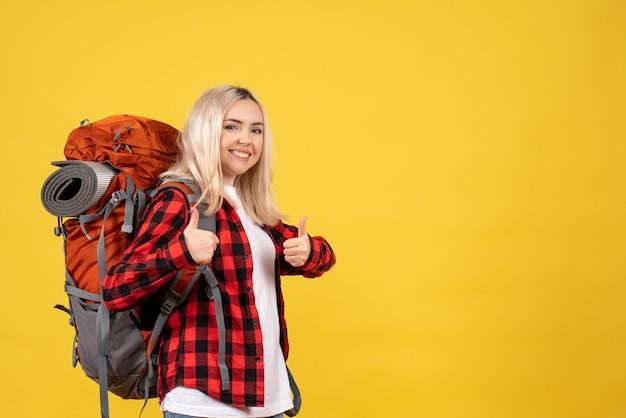 親指をあきらめる彼女のバックパックと正面の金髪の旅行者の女性