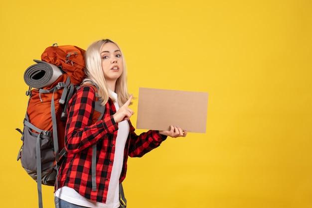 Вид спереди блондинка путешественница с рюкзаком держит картон, стоя на желтой стене