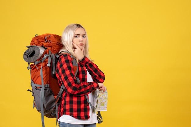 Donna bionda viaggiatore vista frontale con il suo zaino che tiene mappa mettendo la mano sul mento in piedi sul muro giallo