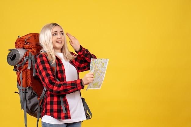 黄色の壁に立っている地図を保持している彼女のバックパックと正面図金髪旅行者の女性