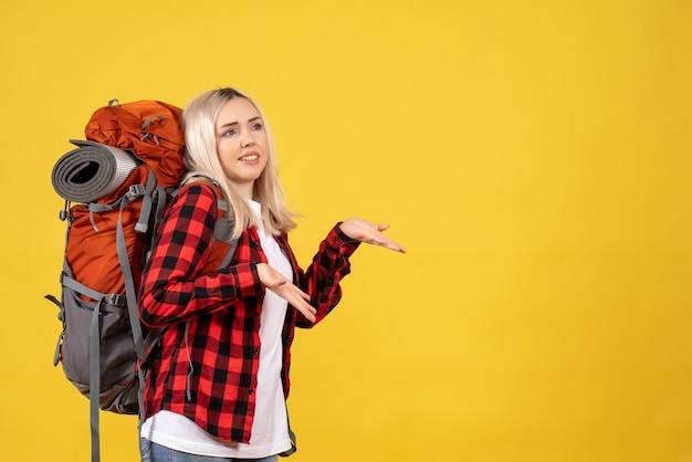 Вид спереди блондинка путешественница с рюкзаком, стоящая на желтой стене