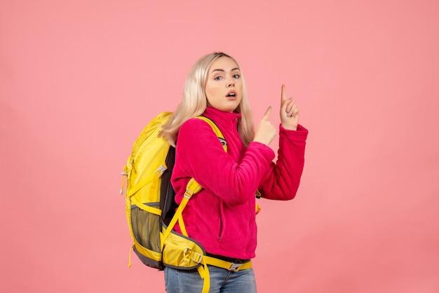 Вид спереди блондинка путешественница с желтым рюкзаком, указывая пальцами вверх