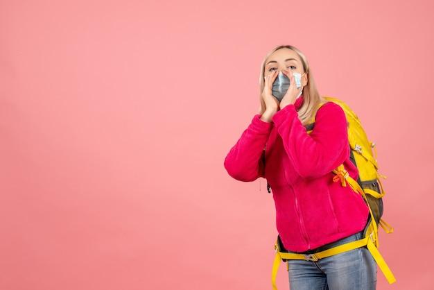 누군가를 호출하는 마스크를 쓰고 노란색 배낭 전면보기 금발 여행자 여자