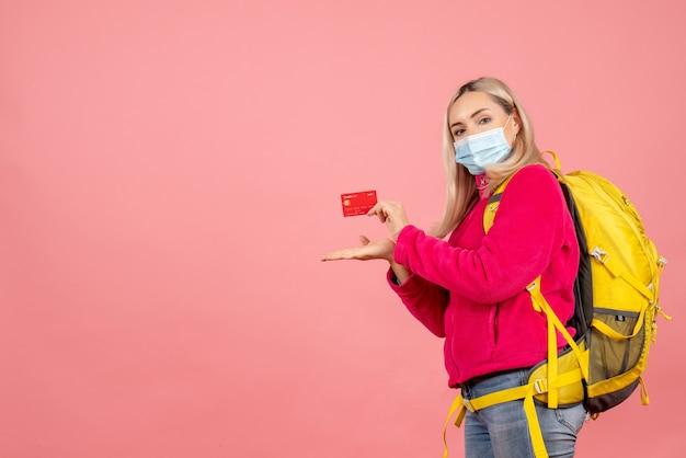 카드를 들고 마스크를 쓰고 노란색 배낭 전면보기 금발 여행자 여자