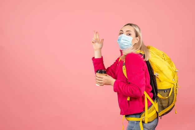 Вид спереди блондинка путешественница с желтым рюкзаком в маске, держащая чашку кофе