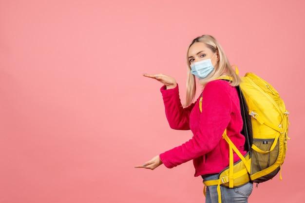手でサイズを示すマスクを身に着けている黄色のバックパックを持つ正面図金髪旅行者の女性