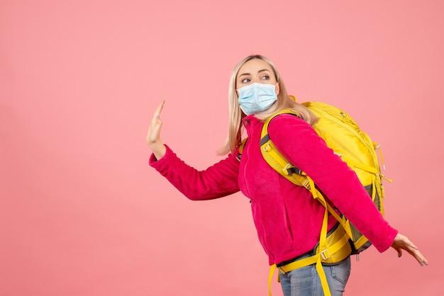 Вид спереди блондинка путешественница с желтым рюкзаком в маске, стоящая на розовой стене