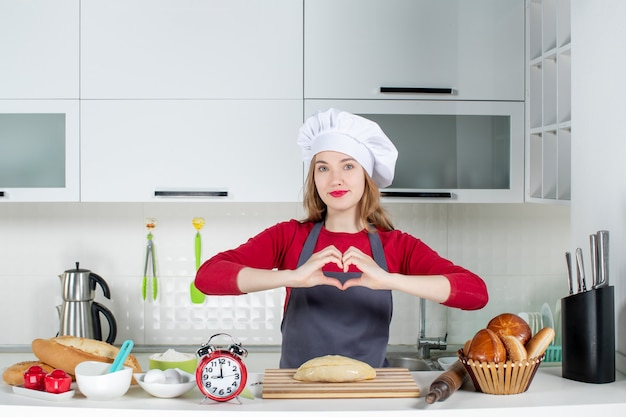 Front view blonde woman in cook hat and apron making heart sign in the kitchen
