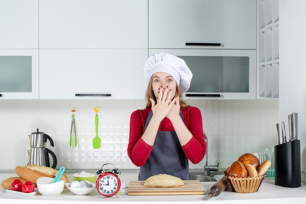 Front view blonde woman in cook hat and apron putting hands on her face in the kitchen