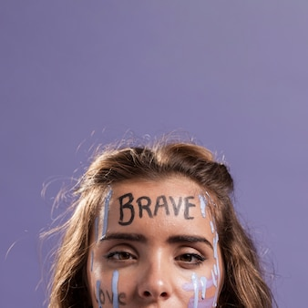 Front view of blonde woman covered with empowering words and paint
