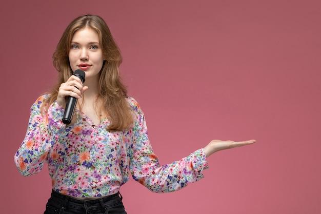 Donna bionda di vista frontale che dà la mano vuota e parla al pubblico