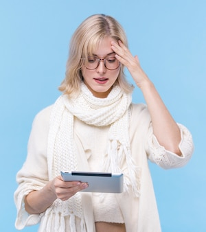 Front view blonde woman holding a tablet