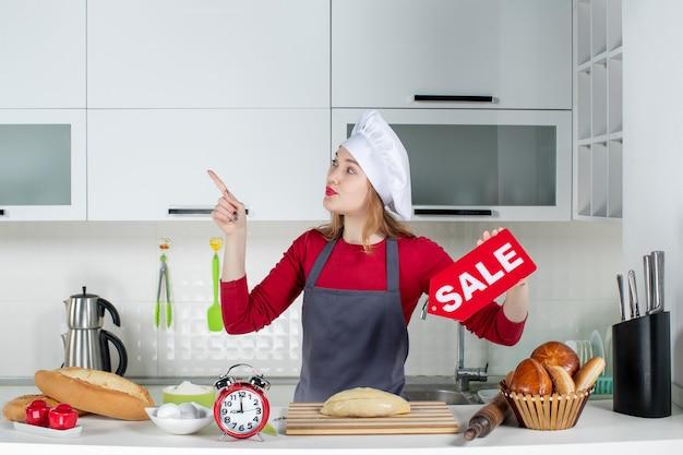 キッチンで赤いセールサインを保持している料理人の帽子とエプロンの正面図金髪女性