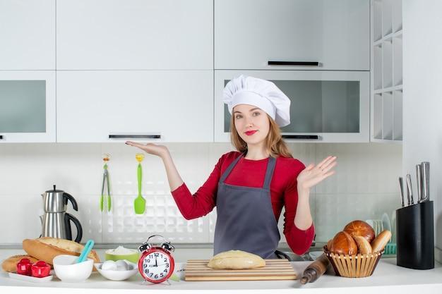 台所のテーブルの後ろに立っているクック帽子とエプロンの正面図金髪女性