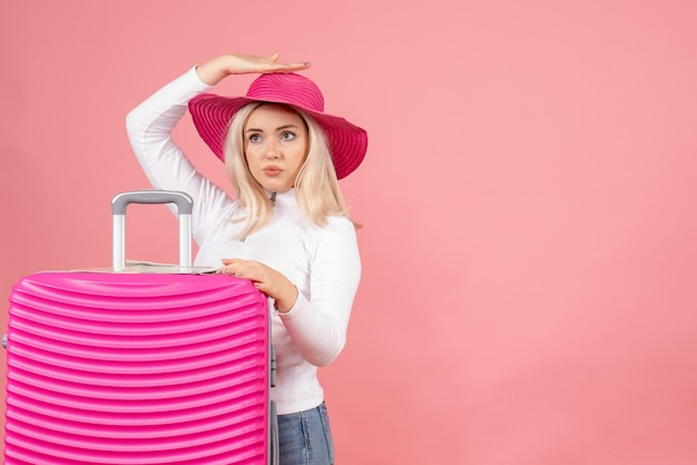 彼女のスーツケースを保持しているピンクのパナマ帽の正面図金髪女性