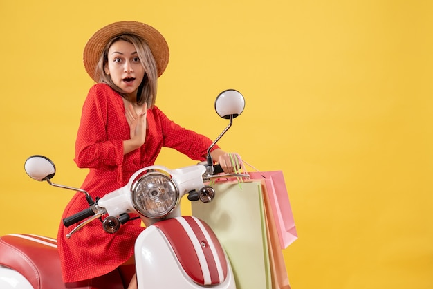 Front view of blonde woman in red dress on moped holding shopping bags pointing at herself