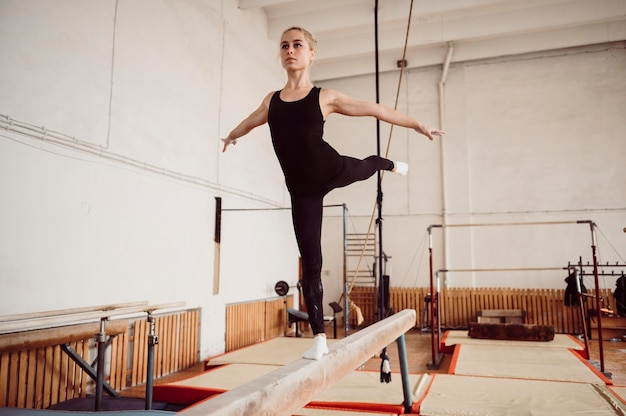 Front view blonde woman training on balance beam