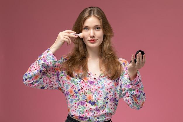 正面図金髪女性は彼女の顔のメイクアップに彼女のパウダーブラシを使用しています