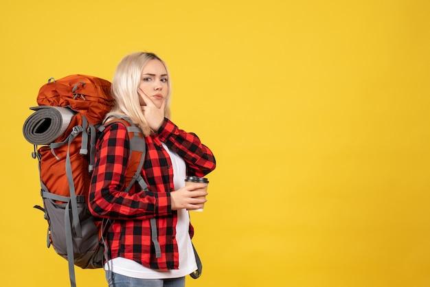彼女のあごに手を置いてコーヒーカップを保持しているバックパックと正面図金髪の女性