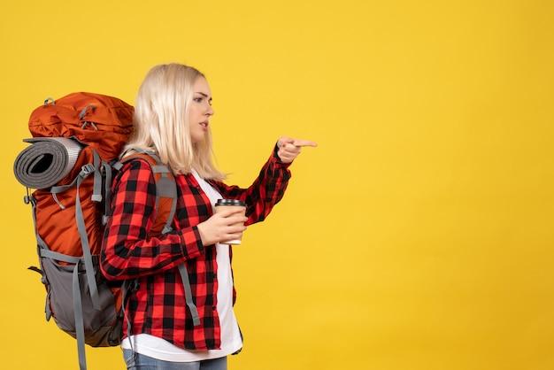 Donna bionda di vista frontale con il suo zaino che tiene tazza di caffè che indica con le dita a destra