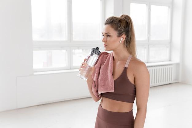 Vista frontale della donna bionda con la bottiglia di acqua