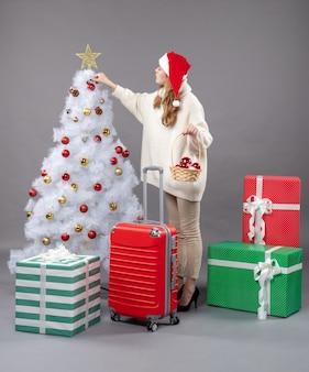 Вид спереди блондинка рождественская девушка держит корзину с рождественскими игрушками возле рождественской елки
