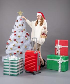 Вид спереди блондинка рождественская девушка держит корзину с рождественскими игрушками, стоящую возле рождественской елки