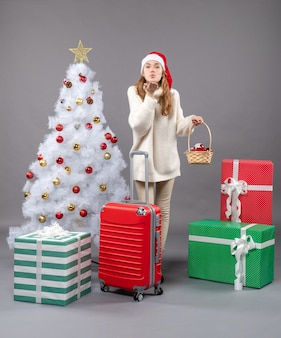 Front view blonde xmas girl holding a gift basket standing near xmas tree
