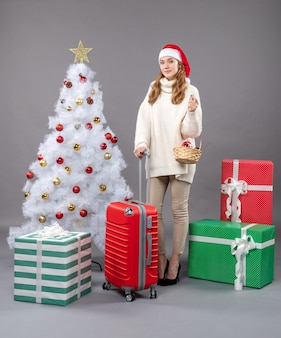 ギフトバスケットを保持しているサンタの帽子と正面の金髪のクリスマスの女性