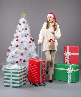 クリスマスのおもちゃとバスケットを保持しているサンタの帽子を持つ正面図金髪のクリスマスの女性
