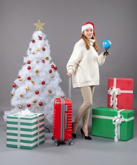 Front view blonde xmas woman with santa hat holding globe standing near xmas tree