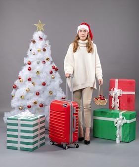 赤いvaliseとクリスマスのおもちゃのバスケットを保持しているサンタの帽子と正面図金髪のクリスマスの女性