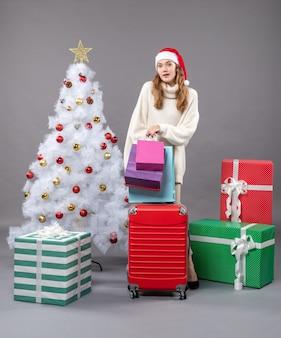 赤いvaliseと買い物袋を保持しているサンタの帽子と正面図金髪のクリスマスの女性