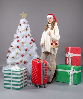 Front view blonde xmas woman with santa hat holding red valise and basket with xmas toys