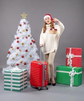ギフトバスケットを見てサンタ帽子をかぶった正面図金髪のクリスマスの女性