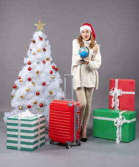 クリスマスツリーの近くの地球を見ているサンタの帽子と正面図金髪のクリスマスの女性